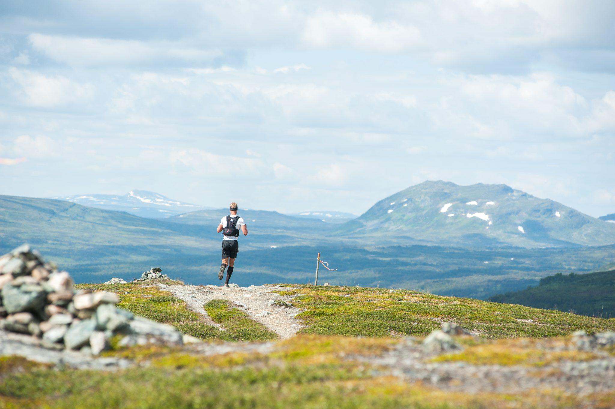 Ramundberget Trail Löpare på väg över fjället med fjälltoppar i bakgrunden